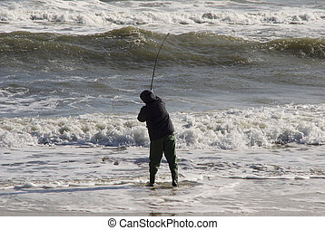 Casting into the Surf - A surf fisherman makes his cast into...