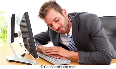 Exhausted businessman sleeping at his desk in the office