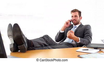 Relaxed businessman putting his feet up talking on the phone...