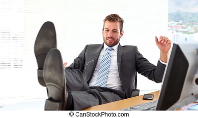 Relaxed businessman putting his feet up smiling at camera in...