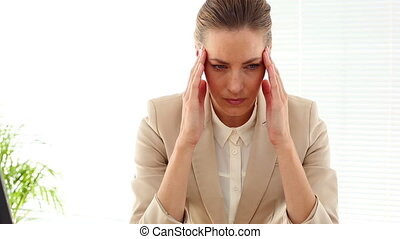 Businesswoman with a bad headache in her office