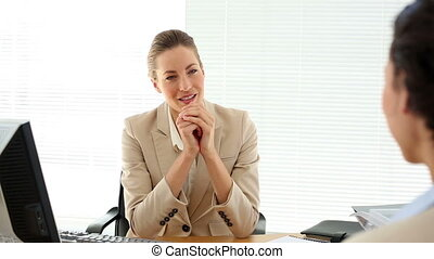 Smiling businesswoman interviewing woman and shaking her...
