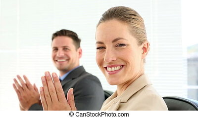 Business people clapping at the camera in the office