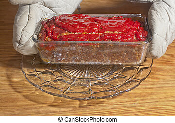 Meatloaf - A hand with oven mitts on serving a hot meatloaf.