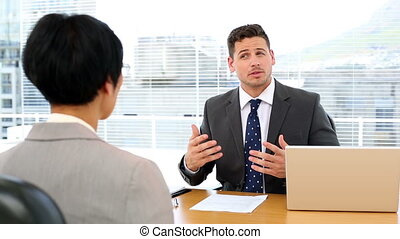 Handsome businessman conducting an interview with...