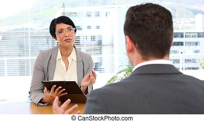 Businesswoman interviewing man at her desk in the office