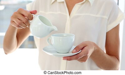 Pretty businesswoman pouring milk into cup in the office
