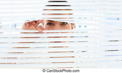 Surprised businesswoman peeking through the blinds in the...