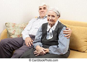 Mature man and senior woman sitting on sofa - Mature man and...