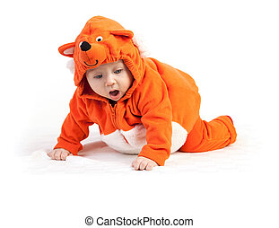 Baby boy in fox costume looking down with surprise over...