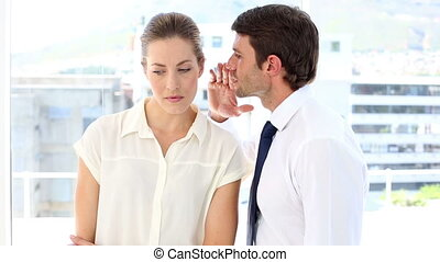 Businessman whispering a secret to his colleague in the...