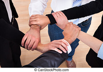 Group Of Businesspeople Holding Wrist - High Angle View Of...