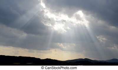Crepuscular rays from flowing clouds which covering the sky