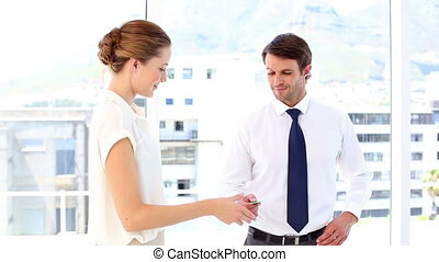 Businessman giving card to businesswoman who shows it to...