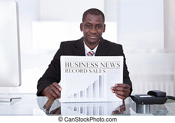 Businessman Showing Newspaper - Young African Businessman At...