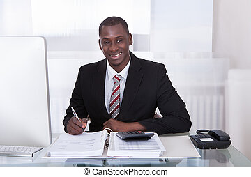 Businessman Calculating Finance - Young African Businessman...