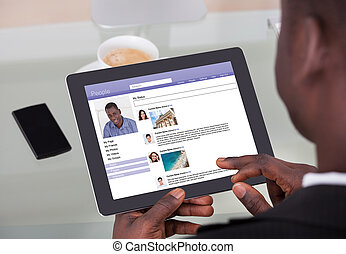 Businessman Chatting On Social Networking Sites Using...