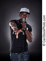 Portrait Of Male Hip-hop Singer Singing Over Black...