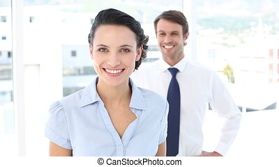 Businesswoman pointing at camera with colleague behind her...