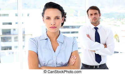 Serious businesswoman looking at camera with colleague...