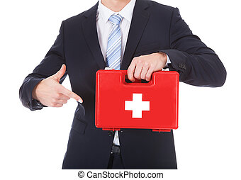 Businessman Pointing At First Aid Box - Close-up Of A...