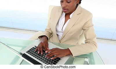 Busy businesswoman using laptop at desk in her office