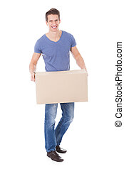 Portrait Of Happy Young Man Holding Cardboard Box Over White...