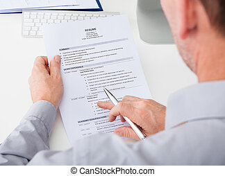 Man Holding Curriculum Vitae - Close-up Of Person Hand...