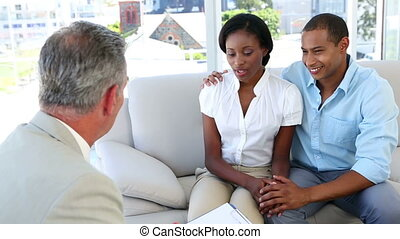 Salesman talking to customers on the couch in the office