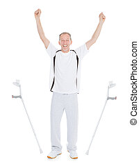 Excited Mature Man Leaving Crutches Over White Background
