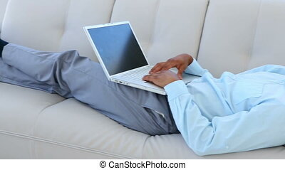 Businessman falling asleep on the couch with laptop in the...