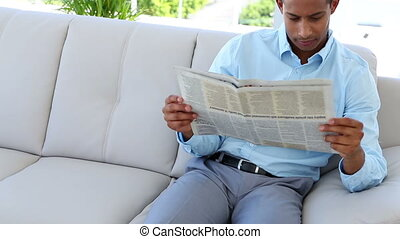 Businessman on couch reading newspaper in the office