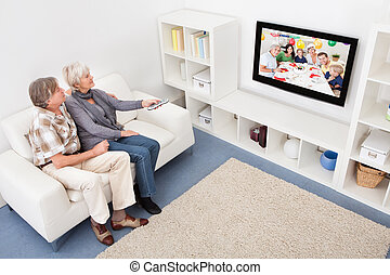 Senior Couple Changing Channel Of Television - Senior Couple...