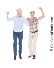 Excited Senior Couple Raising Hand Over White Background