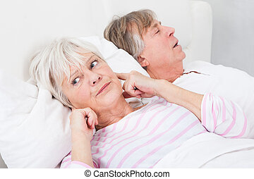 Woman Disturbed With Man Snoring - Portrait Of Senior Angry...