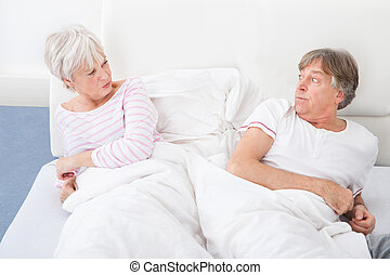 Angry Couple Lying On Bed - Angry Senior Couple Lying On Bed...