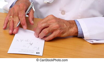 Doctor writing on prescription pad