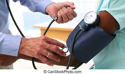 Doctor checking the blood pressure of patient in his office...