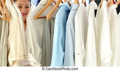 Pretty fashion designer looking at clothing - Pretty fashion...