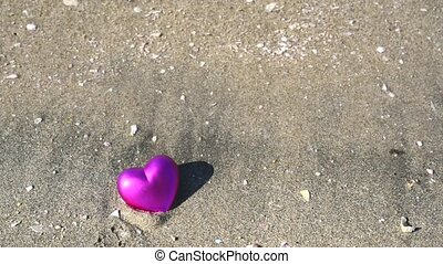 Heart on sandy beach - Pink heart on a sandy beach with...