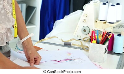 Fashion designer sketching a dress design in her studio