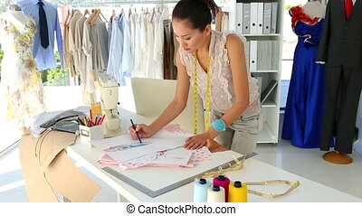 Fashion designer sketching a design at table in her studio