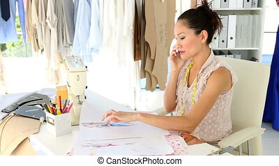 Fashion designer sitting at table talking on phone in her...