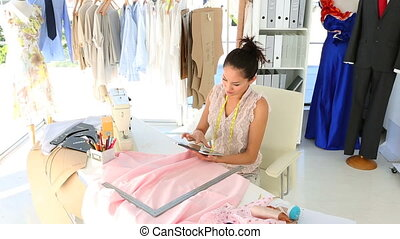 Fashion designer sitting at table using her tablet in her...