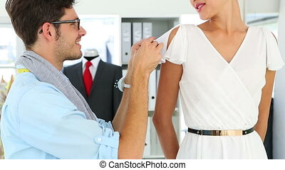 Designer adjusting sleeve of dress on model in his studio