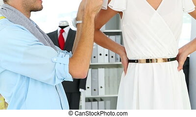 Designer adjusting sleeve of dress on model and smiling at...