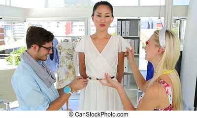 Designers adjusting dress on model while chatting in his...