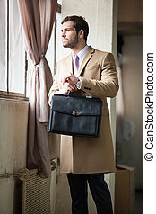 Elegant young businessman looking out the window - Elegant...