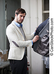 Handsome man wearing a white blazer shopping for clothes at...