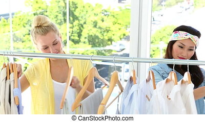 Friends looking through clothing rail together at fashion...